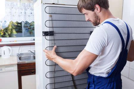 Handyman in blue uniform fixing the fridge