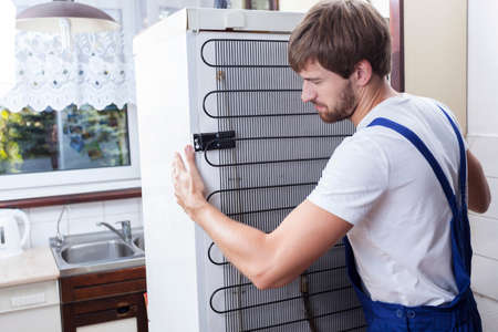 refrigerador: Manitas tratar de mover una nevera en la casa Foto de archivo