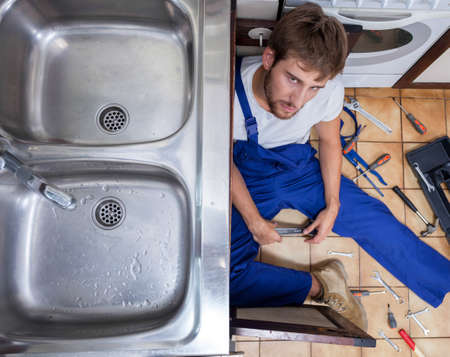 Tired and annoyed handyman during repair sink photo