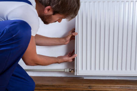 Handyman fix the radiator in the room