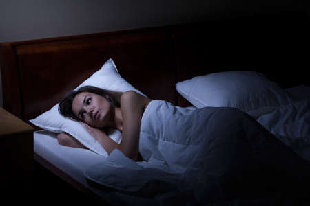 bed linen: Woman suffering from depression at night, horizontal Stock Photo