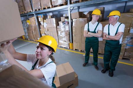 mujer trabajadora: Joven mujer que trabaja en el almac�n y sus colegas perezosos Foto de archivo