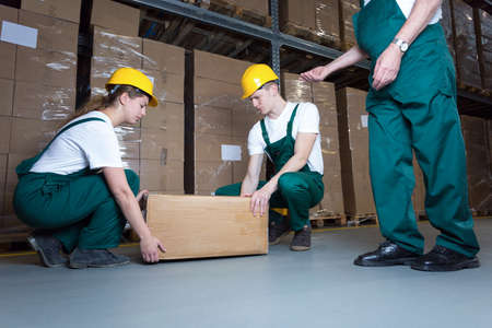 distribution box: Two young workers lifting heavy box in warehouse