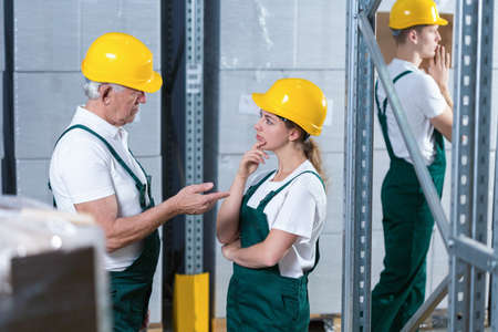 supervisor: Young woman in helmet talking to her older supervisor