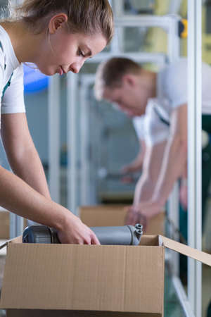 packing supplies: Young girl packing the box in warehouse