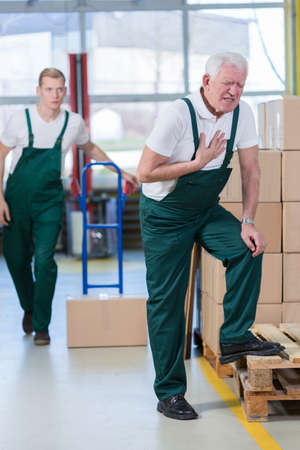 packing supplies: Older warehouseman having pain in his chest