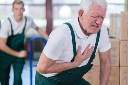 work injury: Close-up of older warehouse worker having a heart attack Stock Photo