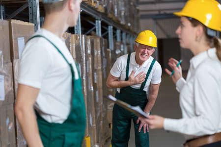 Oudere magazijnier met een pijnlijke infarct Stockfoto