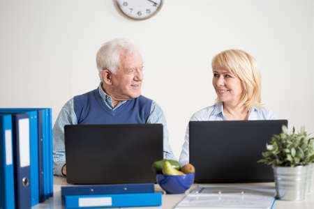 transact: Elderly busy couple running together a business