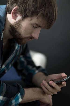 hombre solo: Hombre hermoso joven que revisar los mensajes en su tel�fono inteligente