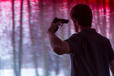 Young depressed man with gun aimed in head