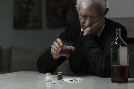 Elderly man addicted to alcohol and drugs photo