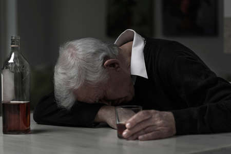 heartbreak issues: Old retired man alcoholic sleeping on the table