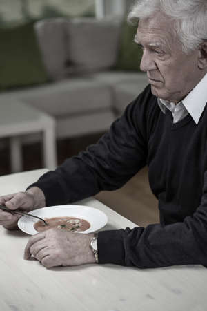 Elderly widower eating meal in loneliness in home photo