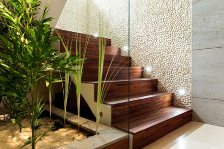 hall: Illuminated wooden staircase in modern house, horizontal Stock Photo