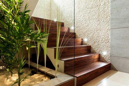 Illuminated wooden staircase in modern house, horizontal Stockfoto