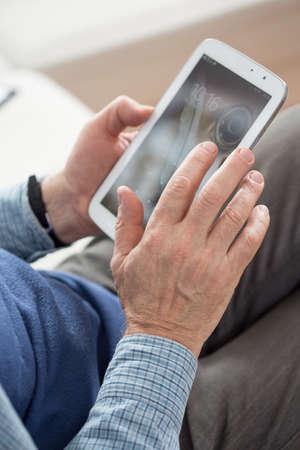 transact: Close-up of senior man using his tablet