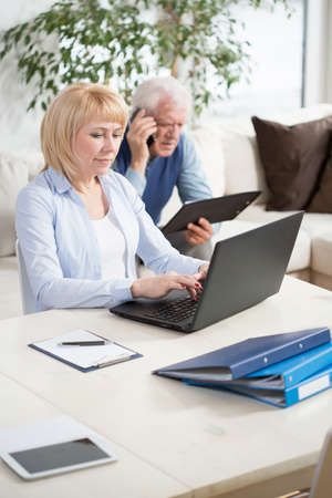 transact: Photo of aged businesspeople working at home