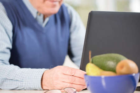 transact: Close-up of aged businessman using laptop