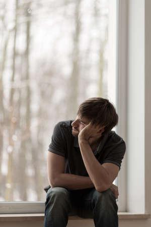 hombre solitario: Joven hombre solitario deprimido mirando por la ventana