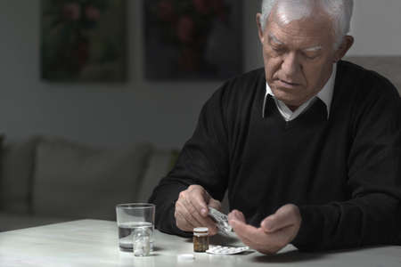miserable: Old aged and sad man taking medicaments
