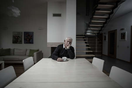Old man lonely in a big empty house Stock Photo