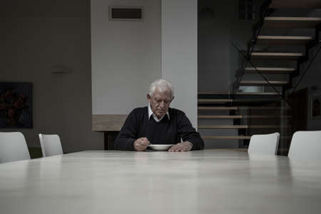 Bejaarde man het eten van het diner compleet alleen in enorme huis Stockfoto