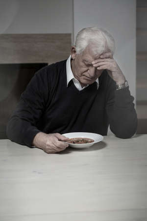 Old aged and lonely man eating soup photo