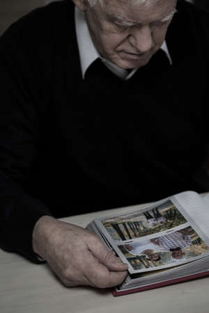 pensionary: Widower in mourn watching photos of his wife