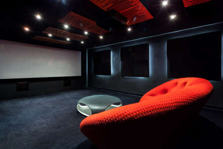 Comfortable red sofa in a dark interior Banco de Imagens