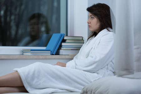 ragazza malata: Foto di giovane donna triste solitario seduto in vestaglia