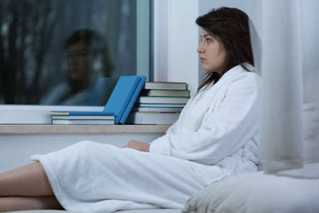 Photo of young lonely sad woman sitting in dressing-gown Stock Photo