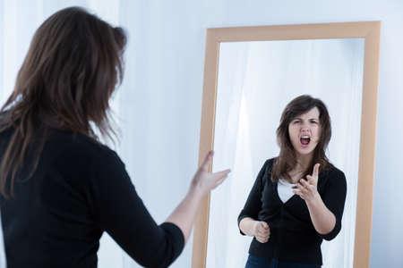 decepción: Mujer enojada joven frente al espejo gritando a sí misma
