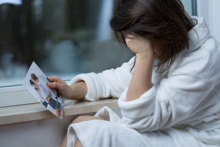 Young broken down woman looking at photo with ex-boyfriend Stock Photo