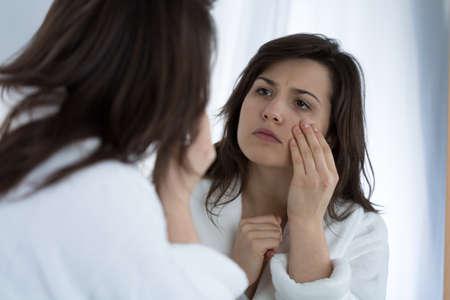 Jonge trieste vrouw in de spiegel kijken op haar rimpels