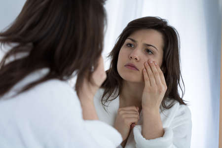 reflection in mirror: Young sad woman looking in the mirror at her wrinkles Stock Photo