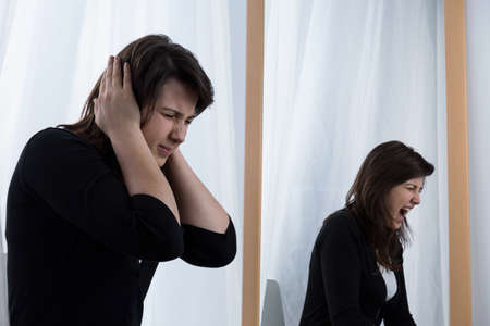dissatisfaction: Young tired woman and her scramming reflection in the mirror