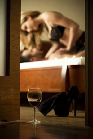 sexuales: Atractiva pareja joven que tiene relaciones sexuales después de una copa de vino