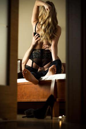man and woman sex: Молодой соблазнительной женщины в сексуальное нижнее белье и ее мужчины Фото со стока