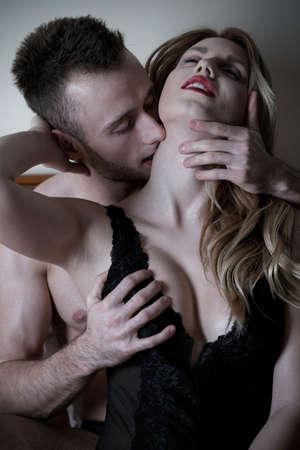 sexo pareja joven: Hombre hermoso joven que besa el cuello de su mujer sexy
