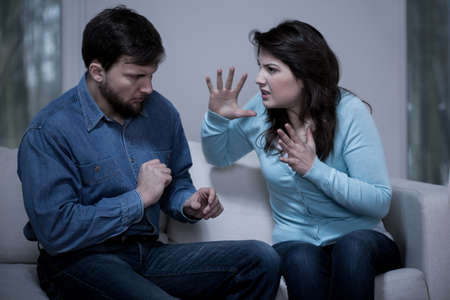 Young man defending himself from his furious wife Stock Photo