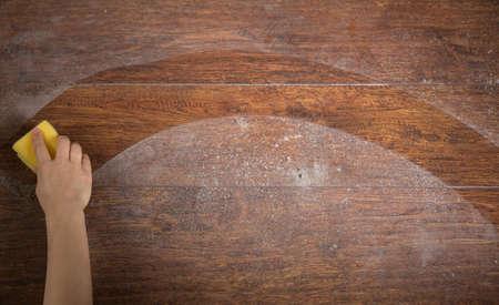 Foto van de hand van de vrouw het schoonmaken van de houten vloer