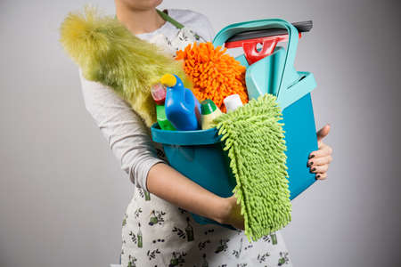 maid: Close-up of woman holding bucket full of cleaners Stock Photo