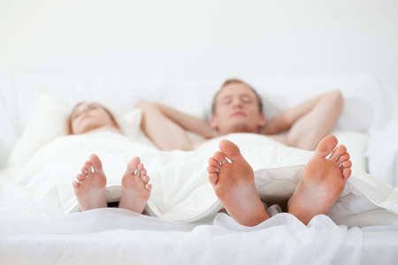 lie: Close-up of the feet of young couple in bed