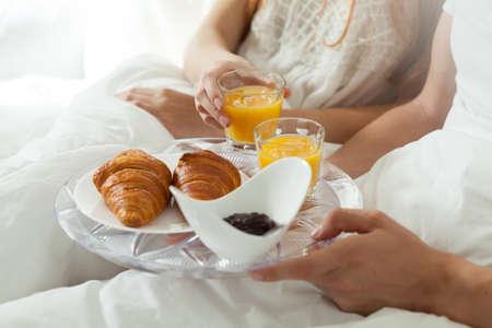amantes en la cama: Comer el desayuno en la cama en la mañana perezosa
