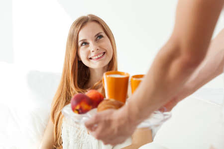 breakfast in bed: Man serving food to young woman in bed Stock Photo