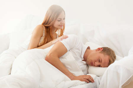 nude wife: Woman gently waking up man in the morning Stock Photo