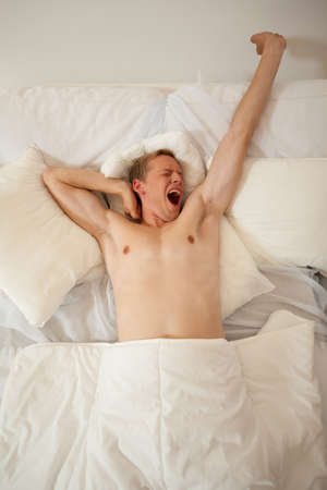 yawning: Man waking up and yawning in bed in the morning