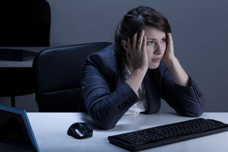 working overtime: Horizontal view of tired businesswoman working overtime Stock Photo