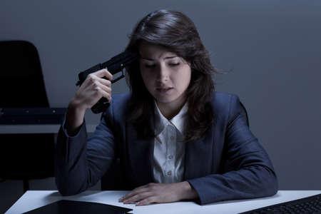 mujer con pistola: Empresaria deprimida que va a suicidarse en la oficina Foto de archivo